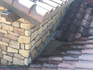 Pigeon netting around stone chimney and roof tiles